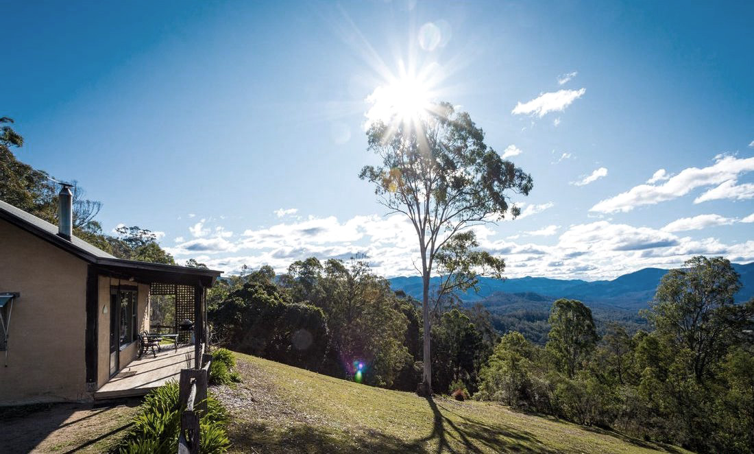 A view of the verandah at Mountain Cottage with the Wadbilliga National Park in the distance